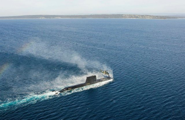 An Australian Submarine conducts personnel transfers with a MRH-90 Taipan helicopter.