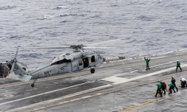 An MH-60S Sea Hawk helicopter assigned to the Chargers of Helicopter Sea Combat Squadron (HSC) 26 takes off from the flight deck of the aircraft carrier USS Theodore Roosevelt (CVN 71).